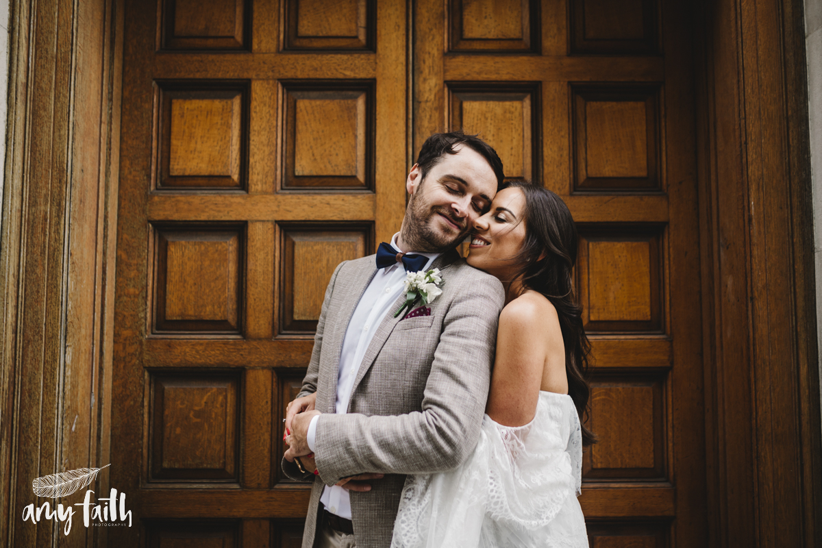 A bride and groom with their eyes closed cuddling in a doorway.