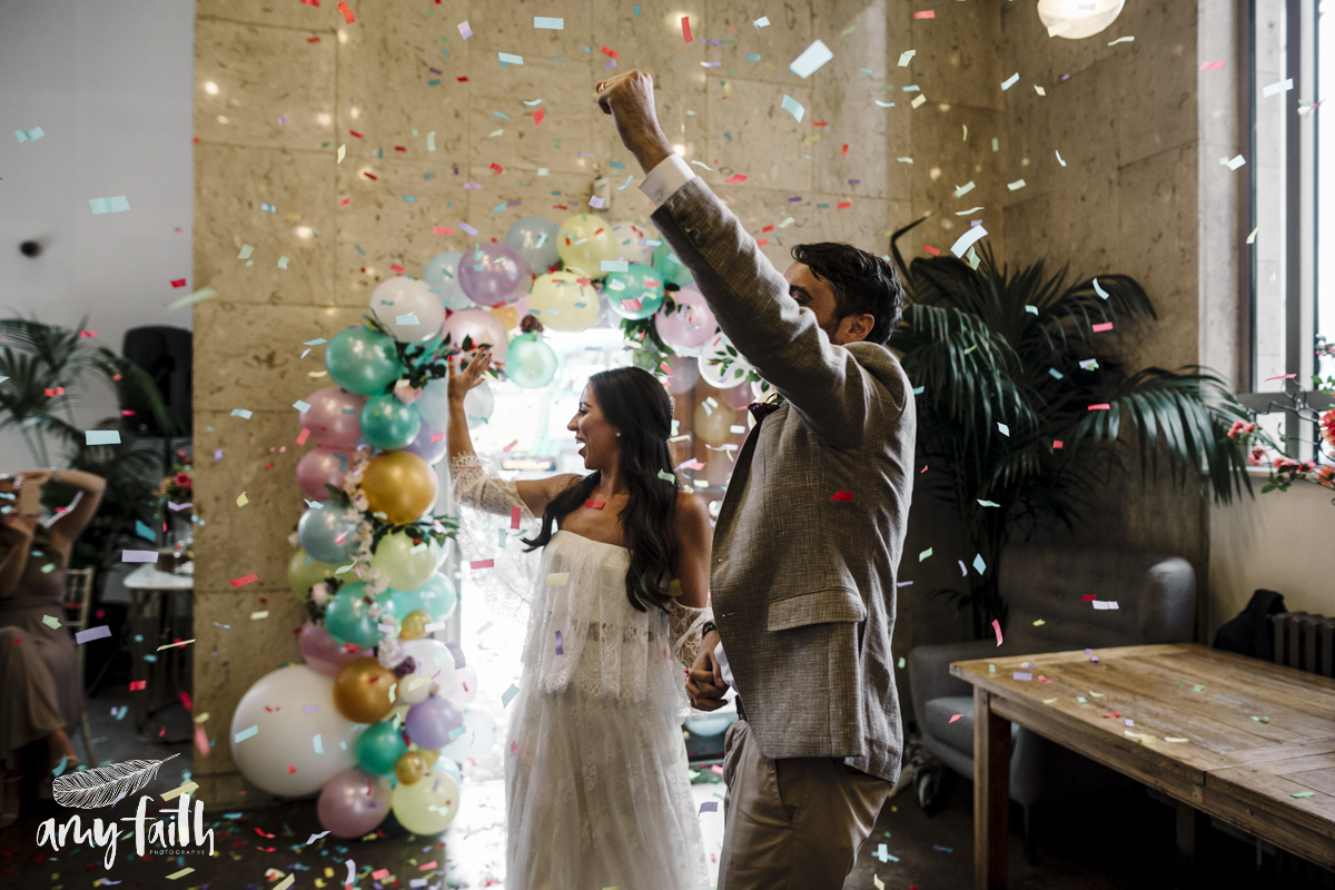 A bride and groom with confetti.