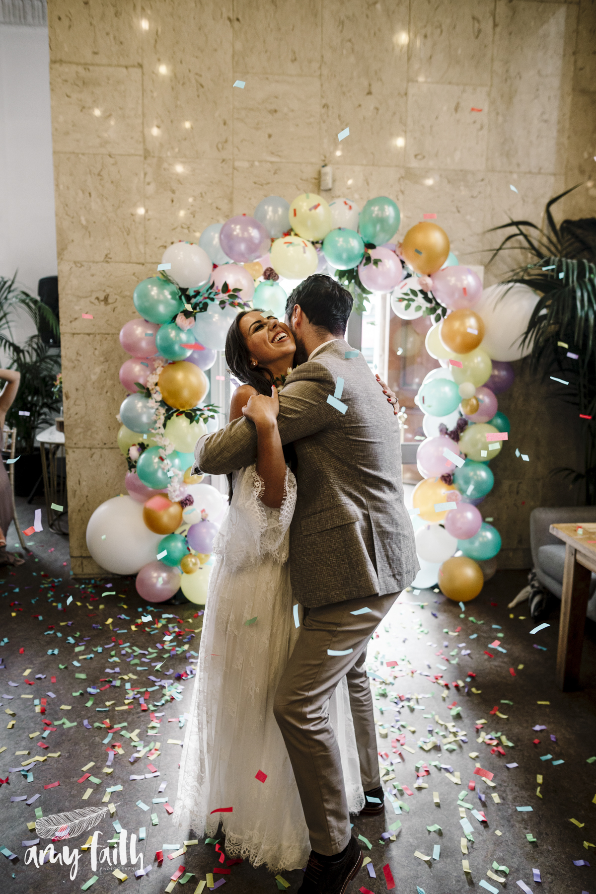 A bride and groom with confetti and balloons.