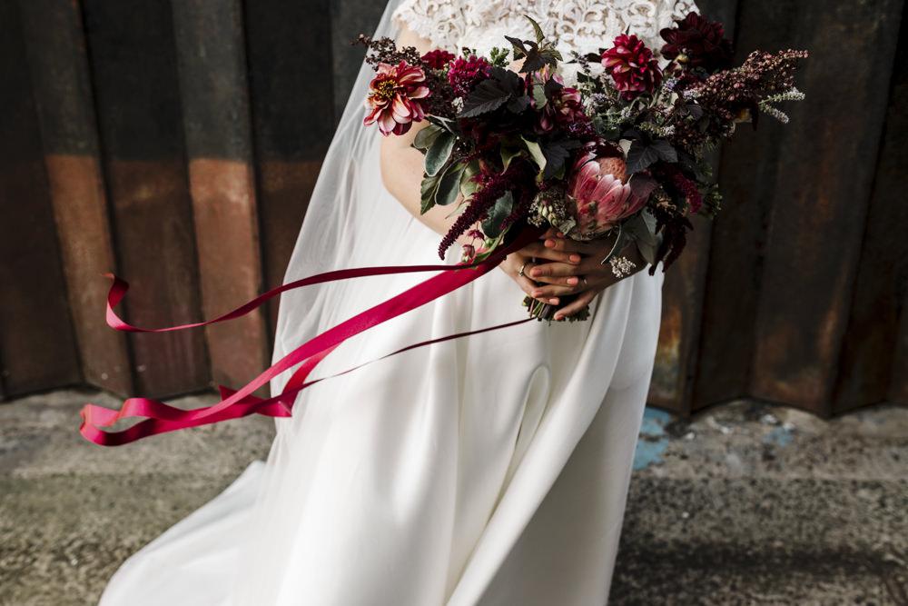 A bride holding a pink bouquet.
